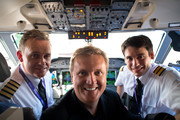 """Aled Jones (C) poses for photographs with flight crew after launching his new Christmas album """"One Voice At Christmas"""" where he performed Walking In The Air and Christmas carols for passengers at 18,000ft on a FLYBE service between London and Cardiff on October 13, 2016 in Cardiff, United Kingdom."""