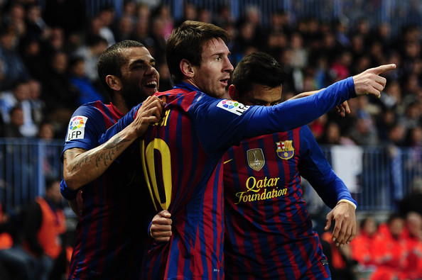 Alexis Sanchez Lionel Messi of FC Malaga (C) celebrates with his teammates Dani Alves (L) and Alexis Sanchez after scoring the opening goal during the La Liga match between Malaga CF and FC Malaga at Rosalada Stadium on January 22, 2012 in Malaga, Spain.