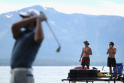 Spectators watch from boats as NFL athlete Aaron Rodgers of the Green Bay Packers tees off during round one of the American Century Championship at Edgewood Tahoe South golf course on July 10, 2020 in Lake Tahoe, Nevada.