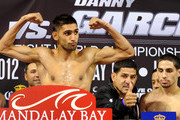 Boxer Amir Khan poses on the scales as Danny Garcia's father and trainer Angel Garcia (C) gives a thumbs up as boxer Danny Garcia looks on during the official weigh-in at the Mandalay Bay Resort & Casino on July 13, 2012 in Las Vegas, Nevada. The two fighters will battle for the WBC/WBA unification super lightweight world championship on July 14 in Las Vegas.