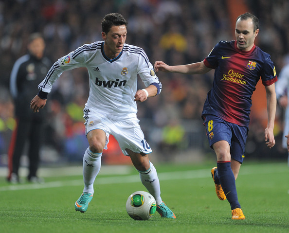 Andres Iniesta Mesut Ozil (L) of Real Madrid CF battles for the ball against Andres Iniesta of FC Barcelona during the Copa del Rey semi final, first leg match between Real Madrid CF and FC Barcelona at Estadio Santiago Bernabeu on January 30, 2013 in Madrid, Spain.