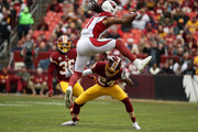 Wide Receiver Larry Fitzgerald #11 of the Arizona Cardinals leaps over cornerback Josh Norman #24 of the Washington Redskins in the first quarter at FedEx Field on December 17, 2017 in Landover, Maryland.