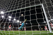 Aaron Ramsey of Arsenal scores past Igor Akinfeev of CSKA Moskva during the UEFA Europa League quarter final leg one match between Arsenal FC and CSKA Moskva at Emirates Stadium on April 5, 2018 in London, United Kingdom.