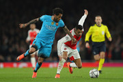 Dani Alves of Barcelona makes a tackle on Alexis Sanchez of Arsenal during the UEFA Champions League round of 16 first leg match between Arsenal and Barcelona on February 23, 2016 in London, United Kingdom.