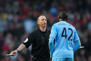 Referee Mike Dean has words with Yaya Toure of Manchester City during the Barclays Premier League match between Arsenal and Manchester City at Emirates Stadium on March 29, 2014 in London, England.