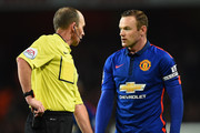 Referee Mike Dean instructs Wayne Rooney of Manchester United (R) over a free kick during the Barclays Premier League match between Arsenal and Manchester United at Emirates Stadium on November 22, 2014 in London, England.