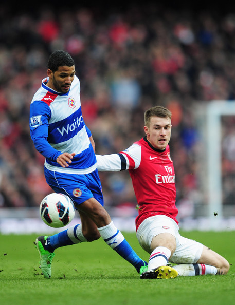 Jobi McAnuff of Reading is tackled by Aaron Ramsey of Arsenal during the Barclays Premier League match between Arsenal and Reading at Emirates Stadium on March 30, 2013 in London, England.