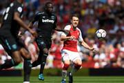 Cheikhou Kouyate of West Ham United and Aaron Ramsey of Arsenal chase the ball during the Premier League match between Arsenal and West Ham United at Emirates Stadium on April 22, 2018 in London, England.