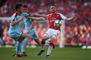 Aaron Ramsey of Arsenal is challenged by Kevin Long of Burnley during the Premier League match between Arsenal and Burnley at Emirates Stadium on May 6, 2018 in London, England.