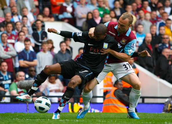 Ashley Young Ashley Young of Aston Villa holds off the challenge by Lars Jacobsen of West Ham United during the Barclays Premier League match between West Ham United and Aston Villa at the Boleyn Ground on April 16, 2011 in London, England.