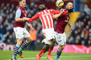 Mame Biram Diouf of Stoke City and Ron Vlaar of Aston Villa (R)  battle for the ball during the Barclays Premier League match between Aston Villa and Stoke City at Villa Park on February 21, 2015 in Birmingham, England.