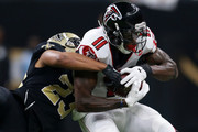 Julio Jones #11 of the Atlanta Falcons is tackled by Marshon Lattimore #23 of the New Orleans Saints during the first half of a game at the Mercedes-Benz Superdome on December 24, 2017 in New Orleans, Louisiana.