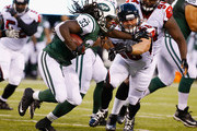 Chris Ivory #33 of the New York Jets runs against Brooks Reed #56 of the Atlanta Falcons  during their pre season game at MetLife Stadium on August 21, 2015 in East Rutherford, New Jersey.