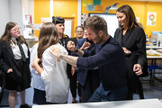 David Beckham signs a pupils shirt as the BFC launch fashion studio apprenticeship with ambassadorial president, David Beckham,  ambassador for positive fashion, Adwoa Aboah and designers Richard Quinn, Rosh Mahtani and Paolino Russo at Prendergast Vale School on September 23, 2019 in London, England.