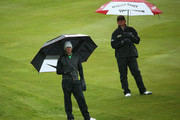 Rory McIlroy of Northern Ireland (L) and Paul Lawrie of Scotland wait to play as the rain falls during the second round of the BMW PGA Championship on the West Course at Wentworth on May 24, 2013 in Virginia Water, England.