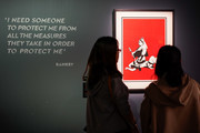A Banksy quote is seen on the wall as visitors look at an art piece at the 'Banksy Genius or Vandal?' exhibition at Asobuild on March 27, 2020 in Yokohama, Japan. The exhibition, open amid the COVID-19 situation in the Tokyo suburb since March 15, 2020, will close for the coming weekend, responding to the stay-at-home request ordered by Kanagawa and neighboring Tokyo Metropolitan governments.