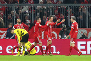 Thomas Mueller of Bayern Muenchen celebrates with teammates James Rodriguez and Robert Lewandowski after scoring his sides second goal during the DFB Cup match between Bayern Muenchen and Borussia Dortmund at Allianz Arena on December 20, 2017 in Munich, Germany.