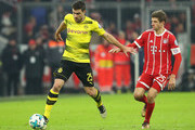 Sokratis Papastathopoulos of Borussia Dortmund runs with the ball under pressure from Thomas Mueller of Bayern Muenchen during the DFB Cup match between Bayern Muenchen and Borussia Dortmund at Allianz Arena on December 20, 2017 in Munich, Germany.