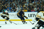 Kyle Okposo #21 of the Buffalo Sabres skates with the puck as Matt Grzelcyk #48 of the Boston Bruins pursues and Jaroslav Halak #41 tends net during the second period at the KeyBank Center on October 4, 2018 in Buffalo, New York.
