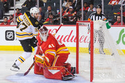 Patrice Bergeron #37 of the Boston Bruins shoots the puck past the net of Mike Smith #41 of the Calgary Flames during an NHL game at Scotiabank Saddledome on October 17, 2018 in Calgary, Alberta, Canada.