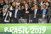 (L-R) President of Brazil Jair Bolsonaro, Paulo Guedes Minister of Economy of Brazil and Cafu sing the national anthem from the stands prior to the Copa America Brazil 2019 Semi Final match between Brazil and Argentina at Mineirao Stadium on July 02, 2019 in Belo Horizonte, Brazil.