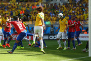David Luiz of Brazil scores his team's first goal against Gonzalo Jara of Chile looks on during the 2014 FIFA World Cup Brazil round of 16 match between Brazil and Chile at Estadio Mineirao on June 28, 2014 in Belo Horizonte, Brazil.