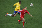 Juan of Brazil chases down Jong Tae-Se of North Korea during the 2010 FIFA World Cup South Africa Group G match between Brazil and North Korea at Ellis Park Stadium on June 15, 2010 in Johannesburg, South Africa.