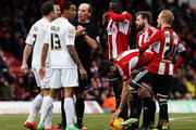 Match referee Mike Dean talks to both sides at a free kick during the Sky Bet Championship match between Brentford and AFC Bournemouth at Griffin Park on February 21, 2015 in Brentford, England.
