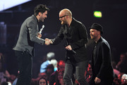 Jonny Buckland and Will Champion of Coldplay recdeive the award for British Live Act from Jack Whitehall on stage during the Brit Awards 2013 at the 02 Arena on February 20, 2013 in London, England.