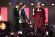Adele with her Best British Female Solo Artist award on stage with award presenters Liam Payne and Louis Tomlinson at the BRIT Awards 2016 at The O2 Arena on February 24, 2016 in London, England.