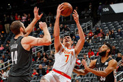 Ersan Ilyasova #7 of the Atlanta Hawks looks to pass as he is defended by Tyler Zeller #44 and Allen Crabbe #33 of the Brooklyn Nets at Philips Arena on January 12, 2018 in Atlanta, Georgia.  NOTE TO USER: User expressly acknowledges and agrees that, by downloading and or using this photograph, User is consenting to the terms and conditions of the Getty Images License Agreement.