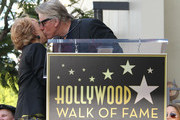 Actor Gary Busey (R) and Maria Elena Holly pose for photographers during the ceremony for recording artist Buddy Holly's posthumous star on the Hollywood Walk of Fame on September 7, 2011 in Hollywood, California.