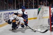 Marcus Foligno #82 of the Buffalo Sabres attempts to wrap the puck arouund the net as he is tripped up by Lubomir Visnovsky #11 of the New York Islanders during the first period at the Nassau Veterans Memorial Coliseum on April 4, 2015 in Uniondale, New York.