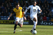 Kelvin Etuhu of Bury looks to play the ball watched by Diego De Girolamo of Northampton Town during the League Two match between Bury and Northampton Town at Gigg Lane on March 21, 2015 in Bury, England.