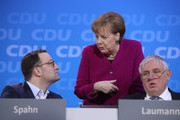 German Chancellor and Chairwoman of the German Christian Democrats (CDU) Angle Merkel chats with colleagues Jens Spahn (L), who has been an outspoken critic of Merkel and is slated to become the next German health minister, and Karl-Josef Laumann at the 30th CDU party congress on February 26, 2018 in Berlin, Germany. The CDU is meeting to confirm the party's coalition contract with the German Social Democrats (SPD) and to elect a new general secretary. The CDU is currently set to go into a government coalition with the SPD in coming weeks. The congress comes the day after Merkel announced her choice of CDU government cabinet members that includes an outspoken critic of Merkel, Jens Spahn.