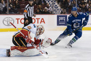 Goalie Mike Smith #41 of the Calgary Flames makes a save while Jay Beagle #83 of the Vancouver Canucks looks for a rebound in NHL action on October, 3, 2018 at Rogers Arena in Vancouver, British Columbia, Canada.