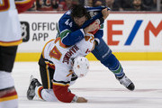 Erik Gudbranson #44 of the Vancouver Canucks knocks down Travis Hamonic #24 of the Calgary Flames during a fight in NHL action on October, 3, 2018 at Rogers Arena in Vancouver, British Columbia, Canada.
