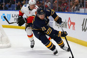 Kyle Okposo #21 of the Buffalo Sabres take the puck behind the net as Brett Kulak #61 of the Calgary Flames pursues during the second period at KeyBank Center on March 7, 2018 in Buffalo, New York.
