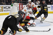 David Perron #57 of the Vegas Golden Knights tries to put a rebound in the net against Mike Smith #41 and Mark Giordano #5 of the Calgary Flames as Michael Frolik #67 of the Flames and Erik Haula #56 of the Golden Knights look on in the second period of their game at T-Mobile Arena on March 18, 2018 in Las Vegas, Nevada. The Golden Knights won 4-0.