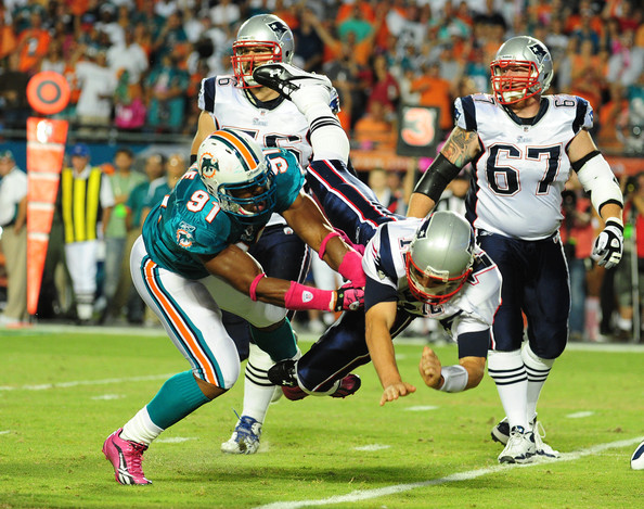 Cameron Wake Tom Brady #12 of the New England Patriots is hit after he passes by Cameron Wake #91 of the Miami Dolphins at Sun Life Field on October 4, 2010 in Miami, Florida.