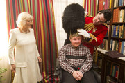 Camilla, Duchess of Cornwall with Samuel Bailey trying on Lieutenant Frederick Lloyd George's hat during a reception at Clarence House hosted by the Duchess of Cornwall, for youngsters and their carers from Helen and Douglas House on December 11, 2013 in London, England.