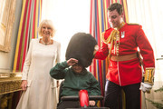 Camilla, Duchess of Cornwall with Daniel Ball trying on Lieutenant Frederick Lloyd George's hat  during a reception at Clarence House hosted by the Duchess of Cornwall, for youngsters and their carers from Helen and Douglas House on December 11, 2013 in London, England.