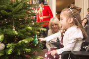 Maya Czerminska helps Camilla, Duchess of Cornwall decorate a Christmas Treeduring a reception at Clarence House hosted by the Duchess of Cornwall, for youngsters and their carers from Helen and Douglas House on December 11, 2013 in London, England.