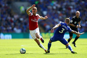 Aaron Ramsey of Arsenal evades Joe Bennett of Cardiff City during the Premier League match between Cardiff City and Arsenal FC at Cardiff City Stadium on September 2, 2018 in Cardiff, United Kingdom.