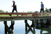 Phil Mickelson and John Rahm of Spain walk across a bridge on the 15th hole during practice for the CareerBuilder Challenge at the Jack Nicklaus Tournament Course at PGA West on January 17, 2018 in La Quinta, California.