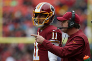 Head coach Jay Gruden of the Washington Redskins talks with quarterback Alex Smith #11 on the sidelines during the first quarter against the Carolina Panthers at FedExField on October 14, 2018 in Landover, Maryland.