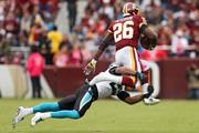 Running back Adrian Peterson #26 of the Washington Redskins loses his shoe as he rushes past strong safety Eric Reid #25 of the Carolina Panthers during the second quarter at FedExField on October 14, 2018 in Landover, Maryland.