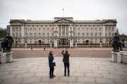A tourist stops to take a photograph of Buckingham Palace on the day that Queen Elizabeth II is set to move to Windsor Palace in a bid to avoid the COVID-19 coronavirus pandemic on March 18, 2020 in London, England.