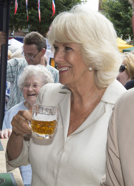 Camilla, Duchess of Cornwall trys a taste of Rutland Bitter as she meets members of the local community and business owners on July 28, 2014 in Oakham, England.