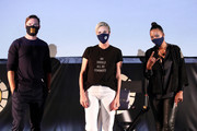 """(L-R) Nicholas Hoult, Charlize Theron, and Aisha Tyler speak onstage at Charlize Theron Hosts Drive-In Screening of """"Mad Max: Fury Road"""" Benefiting the Charlize Theron Africa Outreach Project at The Grove on July 31, 2020 in Los Angeles, California."""